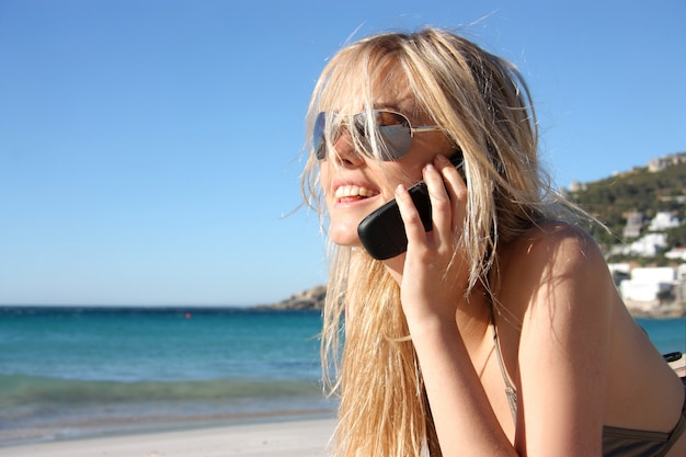 Blond girl at mobile phone on the beach