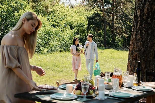 Блондинка кладет тарелку с домашним пирогом на стол, который подают на ужин с друзьями, пока молодая говорящая пара движется по зеленой лужайке