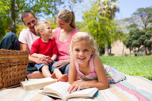 ピクニックのテーブルクロスに横たわって読んでいるブロンドの女の子
