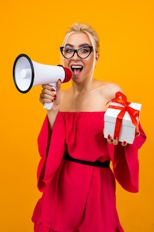 Blond girl in a red dress talks about gifts holding a megaphone and a gift box in hands on a yellow space