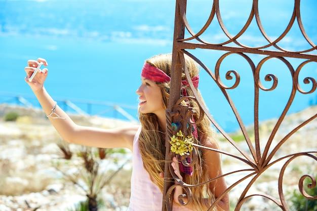 Blond girl selfie photo in mediterranean sea gate