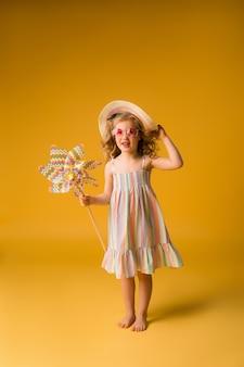 サングラスと風車を保持している夏のサンドレスで笑っているブロンドの女の子