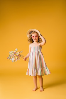 Blond girl smiling in sunglasses and summer sundress holding a windmill