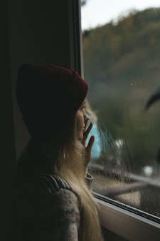 A blond girl standing by the window and looking