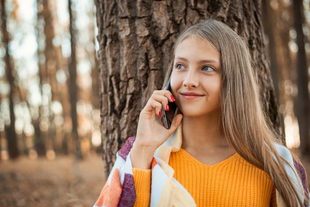 공원에서 전화 통화를 하는 밝은 격자 무늬로 덮인 주황색 스웨터를 입은 금발 소녀