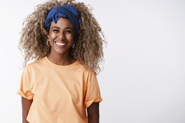 아프로 헤어스타일, 세련된 머리띠, 주황색 티셔츠를 입은 금발 소녀, 웃고 즐겁게 웃고, 흰 벽에 서서 즐겁게 지냅니다.