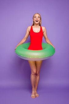 Blond girl with green float around waist isolated on purple