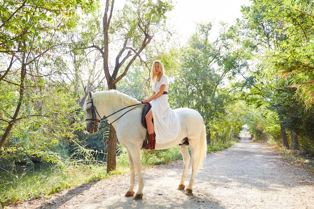 Blond girl woman riding a horse in track