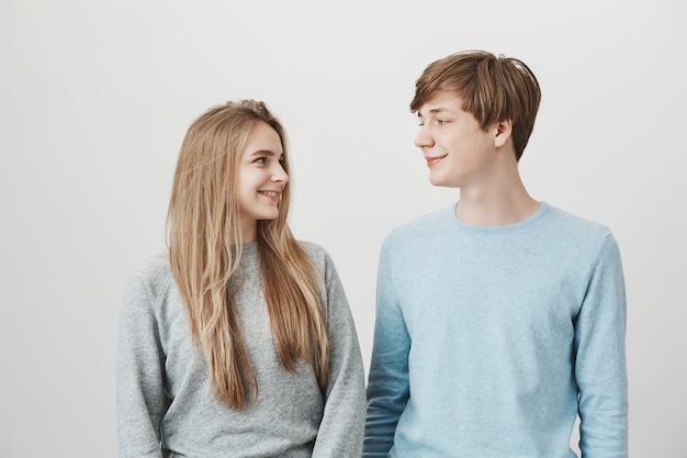 Блондинка и милая девушка, глядя друг на друга, улыбаясь