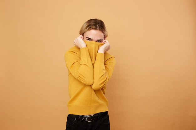 Blond guy dressed in yellow sweater covers his face with a sweater on the beige background in the studio .