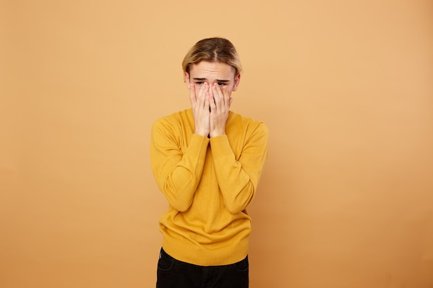 Blond guy dressed in yellow sweater keeps his hands on his face on the beige background in the studio .