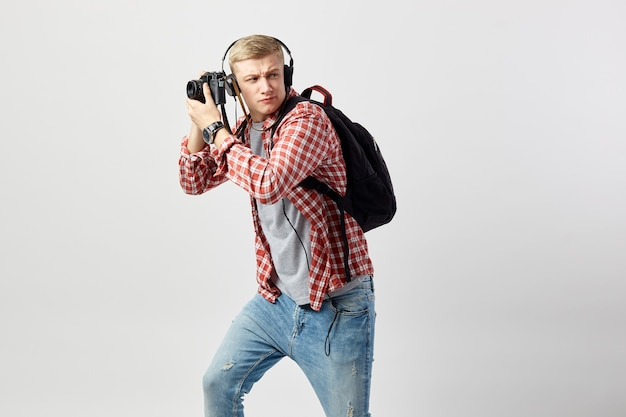 Blond guy in headphones makes photos on camera on the white background in the studio