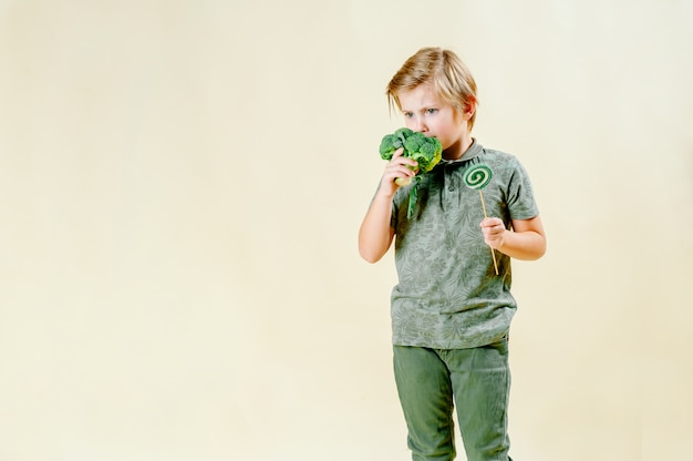 A blond-haired boy holds lettuce in his hand on an isolated , proper nutrition.