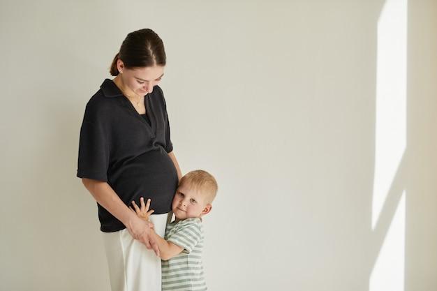금발 머리 소년은 형제 또는 자매의 심장 박동을 들으면서 어머니의 뱃속에 귀를 만지고, 스튜디오 촬영