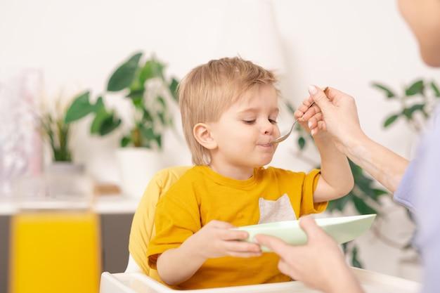 노란색 tshirt에서 blond-haired 어린 소년 유아용 의자에 앉아 어머니가 그를 먹이 동안 숟가락으로 식사