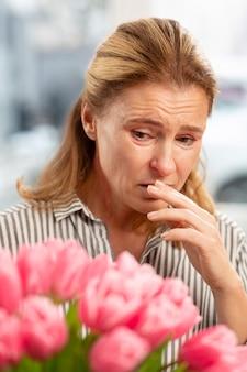 Блондинка зрелая женщина чувствует аллергию после получения цветов от мужа