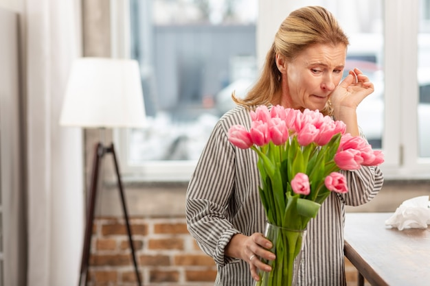 Светловолосая зрелая женщина, держащая вазу с розовыми тюльпанами, чувствует аллергию