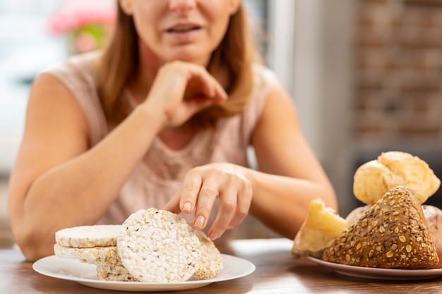 パンの代わりにグルテンフリーのポテトチップスを食べる強いアレルギーを持つブロンドの髪の妻