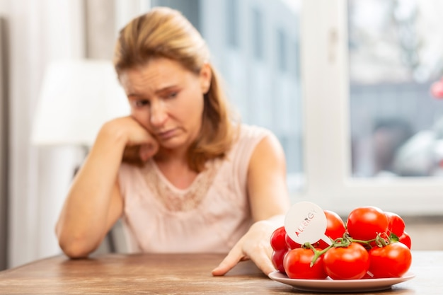 Blond haired woman feeling uncomfortable while having allergy to tomatoes