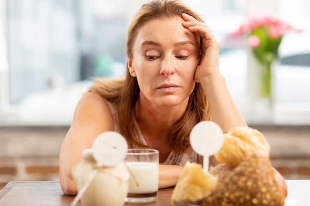 Светловолосая женщина, страдающая аллергией, чувствует себя неудобно и грустно