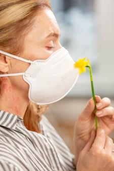 花アレルギーを持っている間保護マスクを身に着けているブロンドの髪の女性