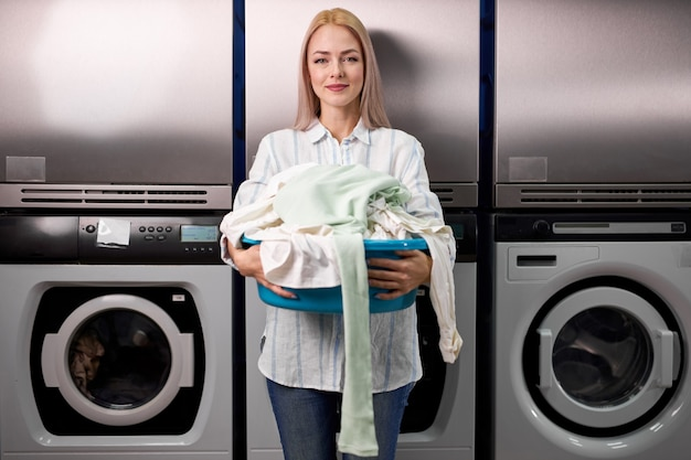 Blond happy woman holding a basket of clothes to be washed in a automatic laundry, young lady stand smiling at camera. washing, cleaning, household chores concept