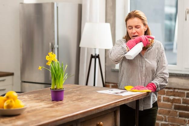 花やほこりに過敏に感じながらくしゃみをする金髪主婦