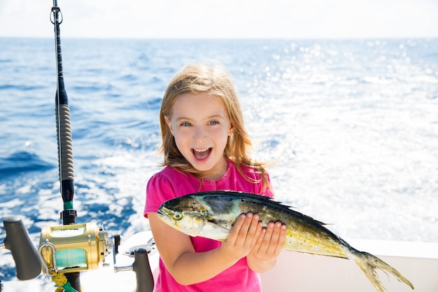 Blond kid girl fishing dorado mahi-mahi fish happy catch
