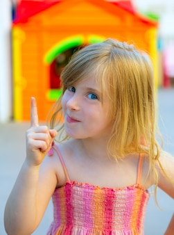 놀이터에서 금발 꼬마 소녀 재미 있은 제스처 손가락