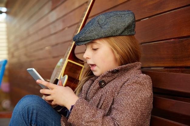 Blond kid girl playing smartphone winter beret