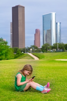 Blond kid girl playing with smartphone sitting on park lawn at city skyline