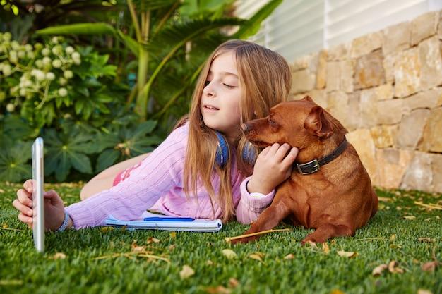金髪の子供女の子selfie写真タブレットpcと犬