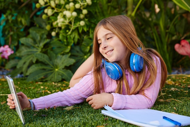 Blond kid girl selfie photo with tablet pc on grass
