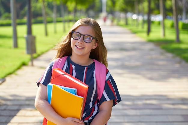 Blond kid student girl in the park with glasses