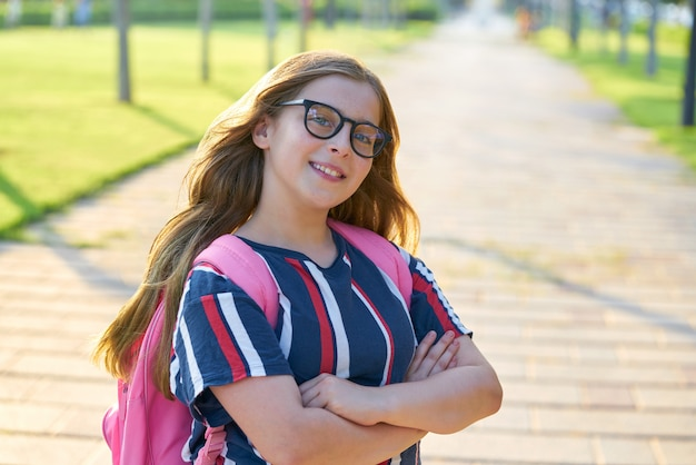 Blond kid student girl with glasses in park