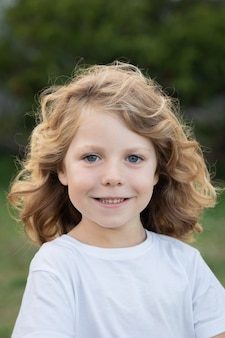 Blond kid with long hair outdoors