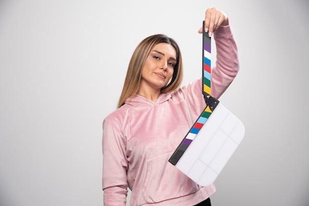 空白のカチンコを保持し、前向きで楽しいポーズを与えるピンクのスウェットシャツの金髪の女性。