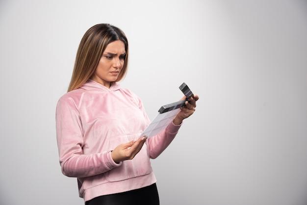 空白のカチンコを保持し、それが何であるかを理解しようとしているピンクのスウェットシャツの金髪の女性