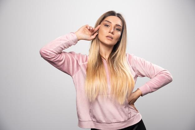 Блондинка в розовой толстовке позирует в элегантной и соблазнительной манере.
