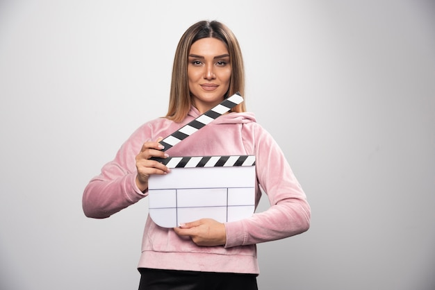 Blond lady in pink sweatshier holding a blank clapper board and gives natural poses.
