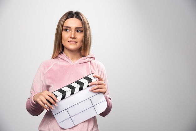 Blond lady in pink sweatshier holding a blank clapper board and gives natural poses