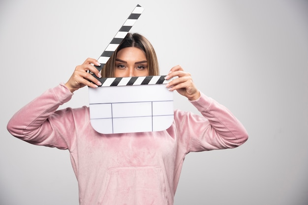 Blond lady in pink sweatshier holding a blank clapper board and looking through it.