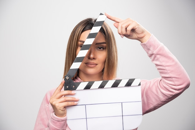 Blond lady in pink sweatshier holding a blank clapper board and looking through it