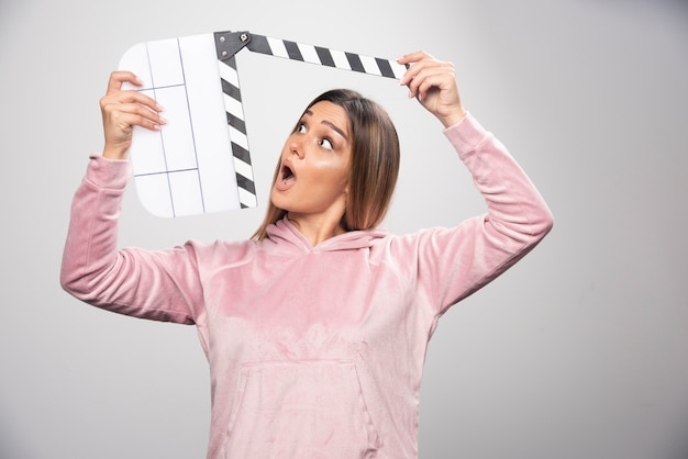 Blond lady in pink sweatshirt holding a blank clapper board looks surprized and confused.