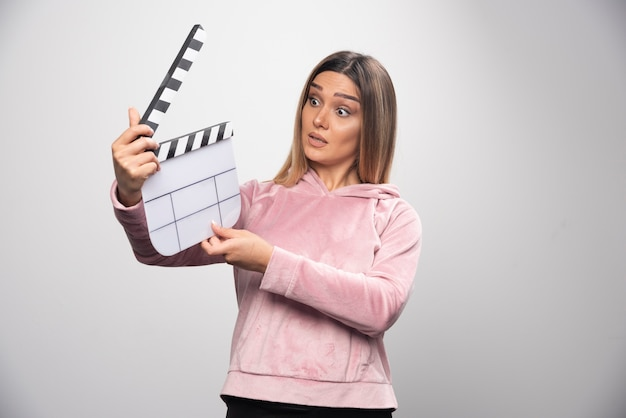 Blond lady in pink sweatshirt holding a blank clapper board and trying to understand what is it.