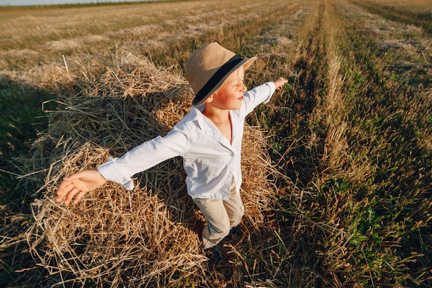 Blond little boy having fun jumping on hay in field. summer, sunny weather, farming. happy childhood. countryside.