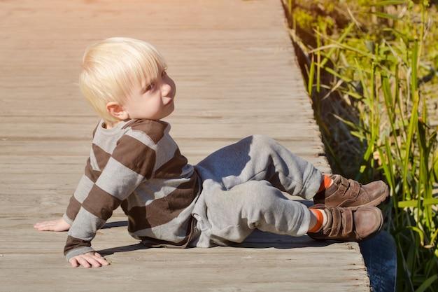 Белокурый маленький мальчик сидит на пирсе осенний солнечный день