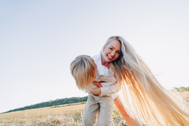 Blond little boy playing with mom with white hair with hay in field. summer, sunny weather, farming. happy childhood.