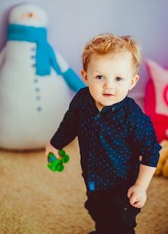 Blond little boy plays on fluffy carpet