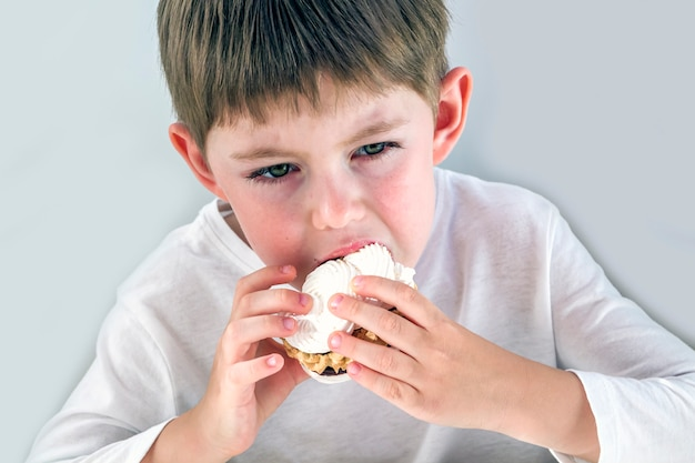 Белокурый маленький мальчик с аппетитом ест вкусный сладкий пирог